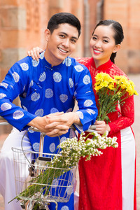 Vietnamese couple in traditional clothes posing on bicycle with flowers