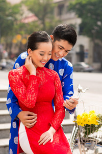 Vietnamese couple in traditional clothes using phone