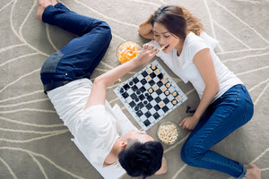 Vietnamese couple lying on the floor and playing chess