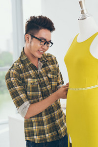 Vietnamese dressmaker measuring a mannequin in yellow dress
