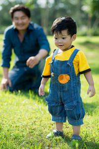 Vietnamese little boy making first steps outdoors