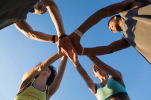 View from below of a group of sporty people in a huddle putting their hands together