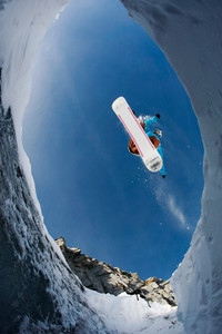 View from below of agile snowboarder in high jump over blue sky