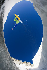View from below of snowboarder jumping over rocky mountainside in winter