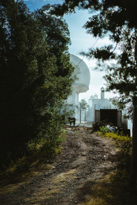 View of a weather station with a large white sphere in coniferous forest on an early morning. Sunbeams are falling on the foot path