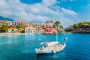 View of beautiful bay of Assos village with fishing boat at anchor in front and clouds in background, Kefalonia island, Greece