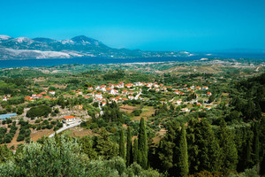 View of idyllic valley town with red roofs on mediterranean island. Olive groves, cypresses and blue bay in the distance