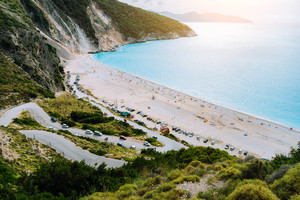 View of serpentine road lead to Famous Myrtos Beach, Kefalonia, Greece. Visiting amazing blue bay during cruise travel trip