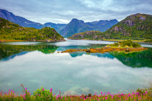 View of the fjord. Rocky seashore with reflection, blue cloudy sky. Beautiful nature Norway.