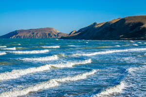 View of the open sea bay. Rocky seashore with blue sky. Beautiful nature.