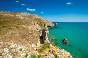View of the open sea. Rocky seashore with blue sky. Beautiful nature