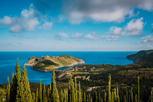 View to Assos village in sun light and beautiful blue sea. Green cypress trees in foreground. Kefalonia island, Greece