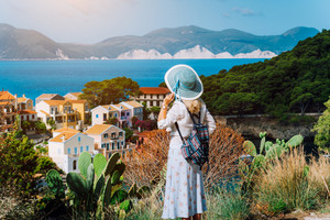 Vintage photo of tourist female wearing blue sun hat and travel backpack enjoying greek coastline in small Assos town. Kefalonia, Greece
