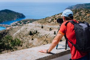 Visiting Kefalonia Greece Europe. Summer holiday weekend. Male freelance photographer with backpack enjoying photography of Mediterranean village Assos from top view point. Camera on tripod