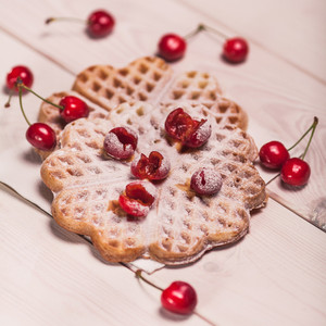Waffles with cherry on white wooden plank