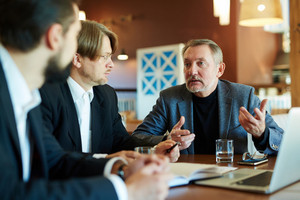 Waist-up portrait of bearded mature businessman expressing his point of view on topical issue under discussion while sitting at cafe table with his coworkers