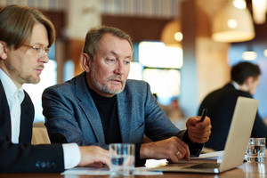 Waist-up portrait of bearded mature entrepreneur sitting next to his colleague in restaurant and looking at laptop screen with concentration