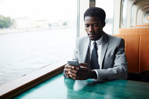 Waist-up portrait of confident Afro-American manager in classical suit texting with friend on smartphone while sitting at middle deck of ship