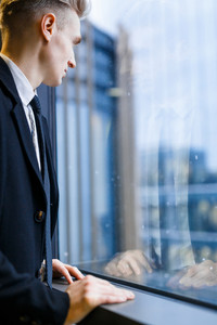Waist-up portrait of confident handsome office worker enjoying view from panoramic window, profile view