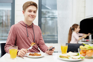 Waist-up portrait of handsome teenage boy looking at camera with wide smile while eating tasty pancakes at breakfast, his little sister standing at sink and washing dishes
