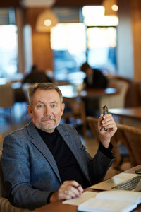 Waist-up portrait of mature manager with slight smile distracted from work in order to pose for photography, spacious cafe with guests on background
