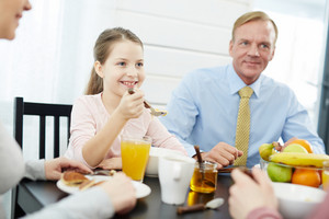 Waist-up portrait of pretty little girl holding spoon with cornflakes in hand and looking at her brother with smile, other family members also enjoying breakfast