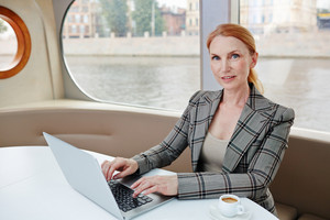 Waist-up portrait of talented middle-aged financial manager posing for photography while preparing annual accounts with help of laptop, interior of cozy middle deck on background