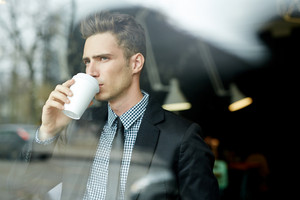 Waist-up portrait of thoughtful young businessman looking out window while standing in office lobby and drinking coffee from paper cup