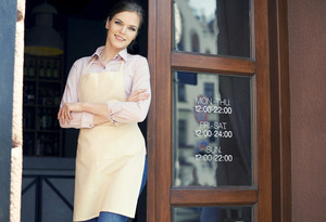 Waitress with arms crossed in front of cafe doors