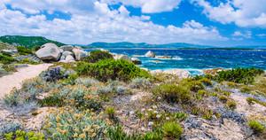 Walking path along sandstone rocksy coastline of Costa Serena, Sardinia, Italy