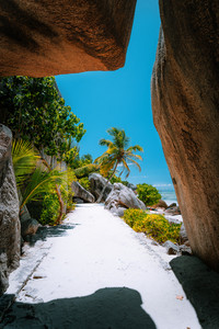 Walking path through giant bizarre granite rock boulders at the famous Anse Source d'Argent beach on island La Digue in Seychelles. Exotic paradise scenery travel concept shot