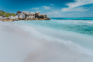 Wave on pristine blue color lagoon with granite rocks on Anse Coco beach, La Digue Island, Seychelles