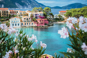 White and lilac flower blossom in front of turquoise colored bay in Mediterranean sea and beautiful colorful houses in Assos village in Kefalonia, Greece