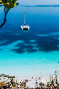White catamaran yacht at anchor on clear azure surface with dark pattern in calm blue lagoon. Unrecognizable tourists relax under sun umbrella on the beach