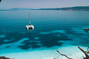 White catamaran yacht at anchor on clear azure water surface in calm blue lagoon. Unrecognizable tourists leisure on the beach