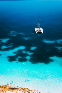 White catamaran yacht drift on clear azure water surface in calm blue lagoon with transparent water and dark pattern on bottom