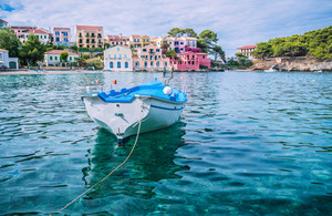 White fishing boat in the blue rippled sea water bay in Assos village, Kefalonia island, Greece