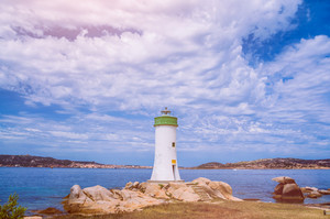 White lighthouse and cloudscape. Sardinia Island, Italy