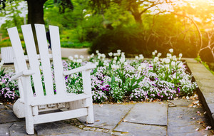 White pleasure chair in City park in Hamburg. Spring time the best time to visit center park planten un blomen during blooming in Hamburg