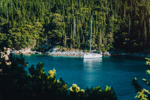 White sail boat yacht moored in the bay of Foki beach with cypress trees in background, Fiskardo, Cefalonia, Ionian, Greece