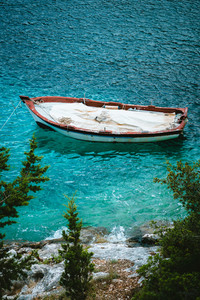 White wooden fishing boat in bay with azure water of Mediterranean sea. White stone shore cypresses trees