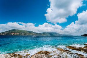 White yacht drift in middle of open crystal clear emerald green sea water near Fiskardo town. Ithaki Island in background. Amazing white cloudscape in blue sky, Kefalonia, Ionian islands, Greece