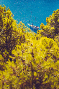 White yacht take a shelter in beautiful blue lagoon of Assos village Kefalonia. Frame between top of the green pine trees. Greece