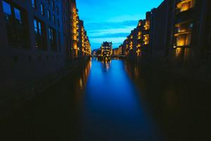 Wide perspective of Warehouse District - Speicherstadt in twilight. Blue hour. Tourism landmark of Hamburg. View of Wandrahmsfleet in light of lantern lamp in HafenCity
