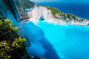 Wide view of Navagio beach with green vegetation in foreground. Famous landscape of Zakinthos island, Greece