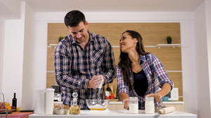 Wife teasing her husband while he's trying to cook for her. Happy couple