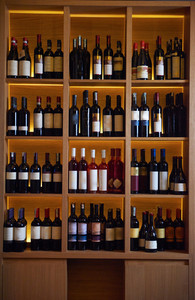 Wine bottles on a wooden shelf in modern restaurant interior