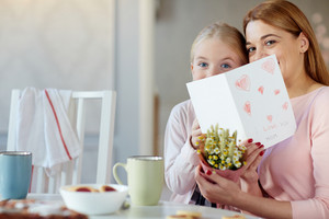 Woman and her daughter holding flowers and handmade greeting-card