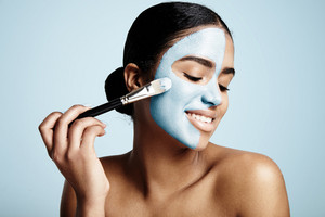 woman applying facial clay mask