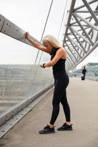 Woman Checking Heart Rate Using Smartwatch After Workout On Bridge